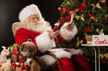 Santa Claus holding envelope and choosing toys from big sack