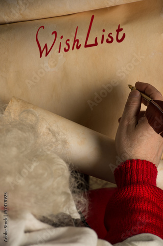 Close-up of Christmas wishlist letter in Santa Claus hands