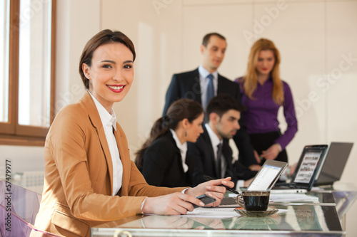 business woman smiling with colleagues in background