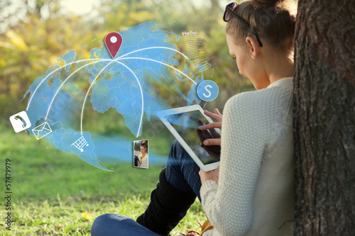canvas print picture young woman using her tablet pc during rest in the park