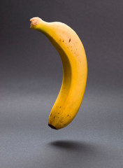 A banana floating in the air in vertical composition