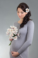 portrait of young beautiful pregnant woman with flowers over gre