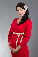 beautiful pregnant woman in red dress over grey background