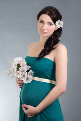 beautiful pregnant woman in green dress over grey background