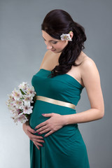 attractive pregnant woman in green dress with flowers over grey