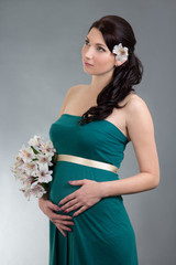 attractive pregnant woman in green dress with flowers dreaming o