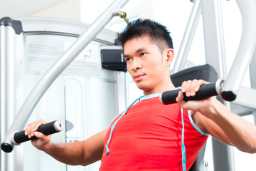 Chinese Man training strength in fitness gym