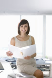 Portrait of smiling businesswoman with folder sitting on desk in office