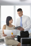 Businessman and businesswoman looking at folder and digital tablet in office
