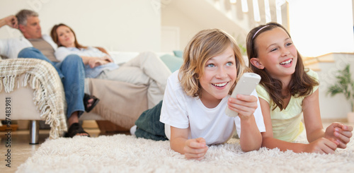 Siblings lying on the floor watching tv