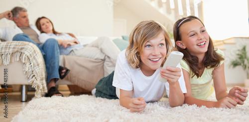 Siblings lying on the floor watching tv Poster