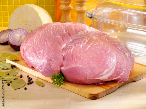 Raw pork ham on kitchen cutting board with glass baking pan