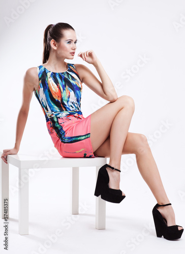young woman in short dress sit on chair, fashion photo