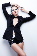 Fashion shoot of young woman in black jacket and leather shorts