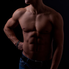 Perfect male body on black background.