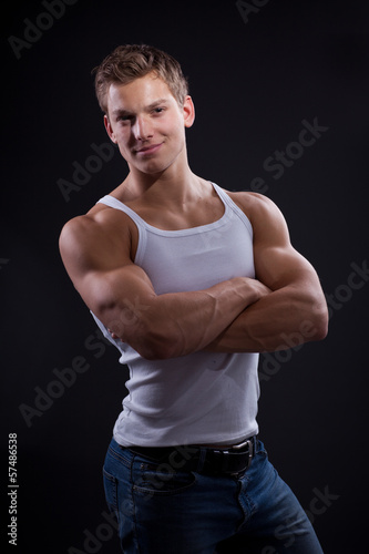 Sexy young man wearing white undershirt and jeans, posing over d