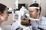 Optometrist examining patient's eyes with eye test equipment