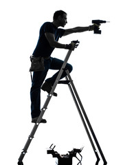 manual worker man on stepladder drilling silhouette