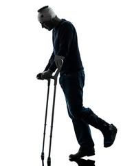 injured man walking sad with crutches silhouette