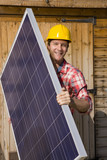 Portrait of smiling engineer holding solar panel