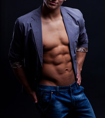 Young sexy macho man with open jacket over dark background