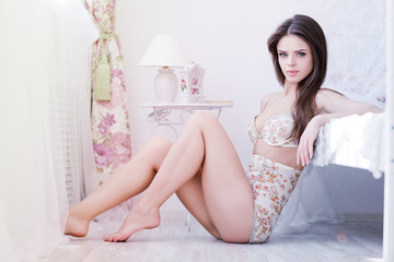 sexy young woman in  lingerie sitting on the floor near the bed.