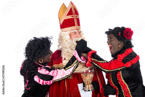 Zwarte Piet giving pepernoten (cookies) to Sinterklaas