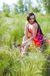 Outdoor portrait of young beautiful woman in red dress and flowe