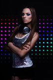 young DJ woman with the headphones over disco background