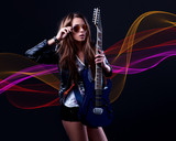 young  woman rockstar with blue electric guitar and sunglasses