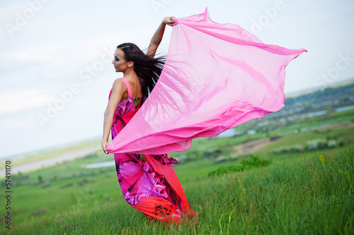 Beautiful young woman on a green field with a colored tissue