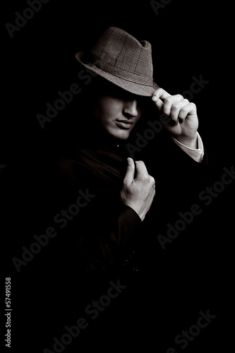 Portrait of young gangster with hat in the darkness