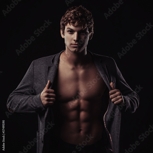 Young handsome macho man with muscle abdominal and open jacket