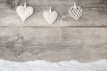 white hearts on wooden background with snowflake