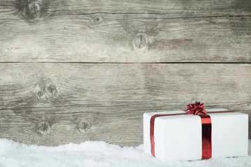 Gift box on an old wooden background with snowflake