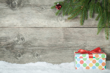Christmas Present on an old wooden background with snowflake