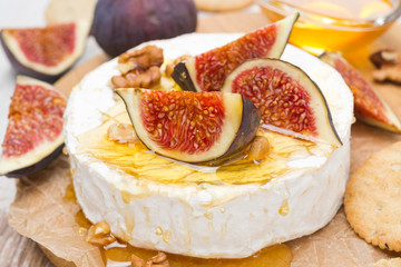 Camembert cheese with honey, figs, walnuts and crackers, closeup