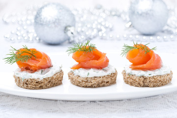 canape with rye bread, cream cheese, salmon for Christmas