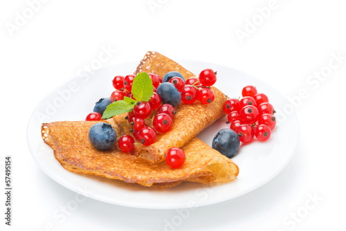 crepes with red currants and blueberries on a plate isolated