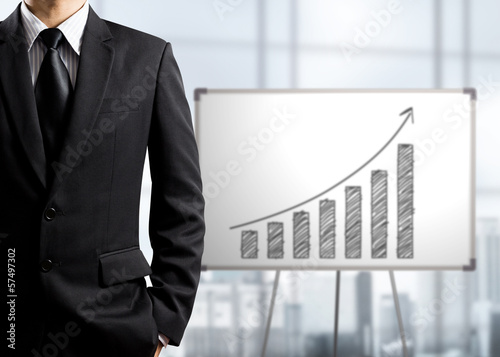 Business man standing and drawing growth chart on white board