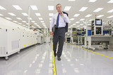 Businessman walking through hi-tech electronics factory