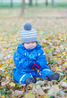sad baby boy sitting on yellow leaves in autumn