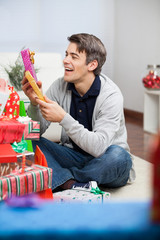Smiling Man Holding Christmas Presents At Home