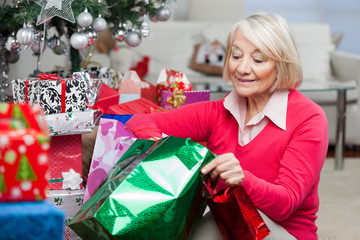 Woman Looking In Bag While Sitting By Christmas Presents