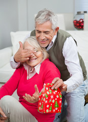 Senior Man Covering Woman's Eyes While Giving Christmas Gift