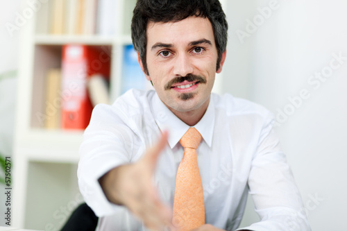 Smiling businessman giving hand for handshake