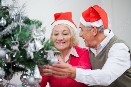 Senior Couple Decorating Christmas Tree