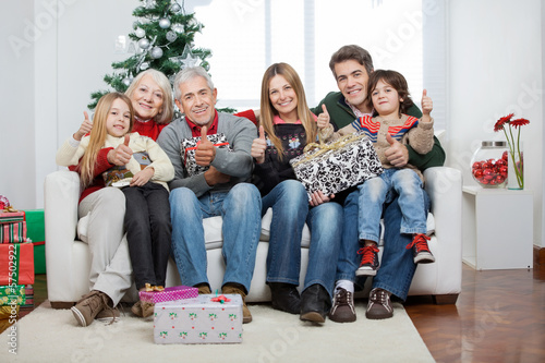 Family With Christmas Presents Sitting On Sofa