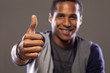 smiling dark-skinned young man showing thumbs up