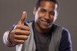 smiling dark-skinned young man showing thumbs up and winks